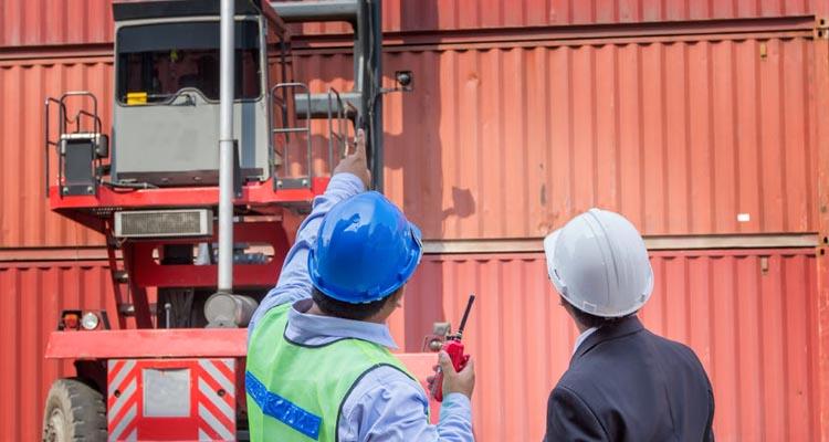 Bedienstete im Hafen überprüfen die Verplombung der Container