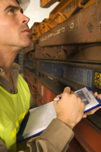 Close-up of a dock worker writing on a clipboard with a pen